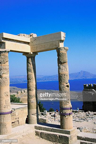 Tourist leaning on Doric column at Doric Temple of Athena Lindia, Lindos, Rhodes, Greece