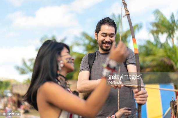 tourist learning lessons, from tupi guarani tribe indigenous, with bow and arrow, brazil - ancient civilization stock photos and pictures