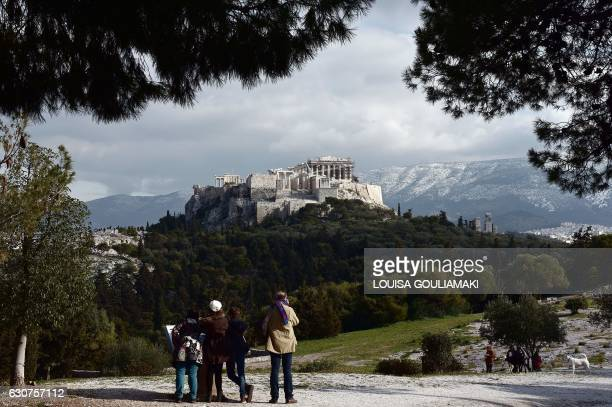 Tourist look over at the ancient Acropolis from the Pnyx Hill in Athens on January 1 2017 / AFP / LOUISA GOULIAMAKI