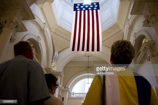 Tourist look up at what is believed to be the oldest American flag with the 13 stars of the 13 original colonies represented as they tour of the...