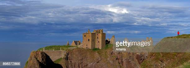 Tourist looking at Dunnottar Castle ruined medieval fortress near Stonehaven on cliff along the North Sea coast Aberdeenshire Scotland UK