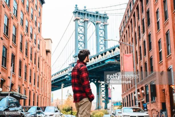tourist looking at manhattan bridge, new york city - チェックシャツ ストックフォトと画像