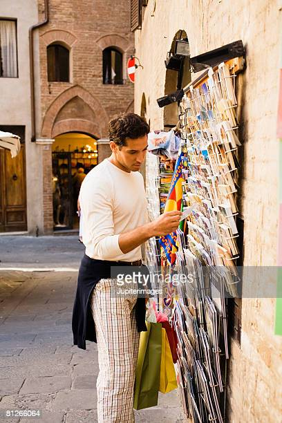 tourist looking at postcards - news stand stock pictures, royalty-free photos & images