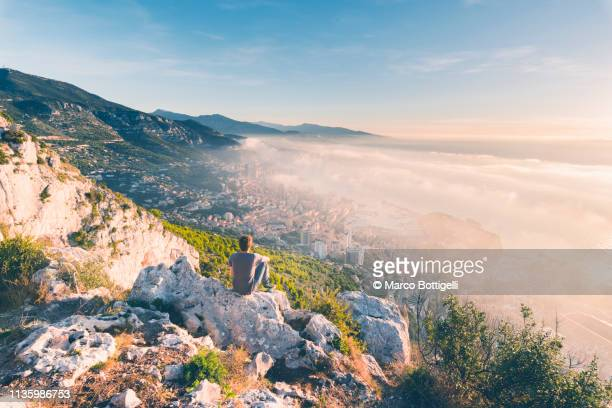 tourist looking at the coastline of monaco at sunrise - monte carlo stock pictures, royalty-free photos & images