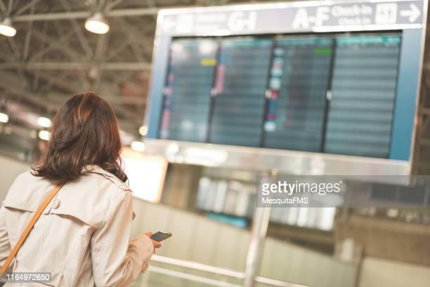 turista mirando el panel de control de vuelo - cambio horario fotografías e imágenes de stock