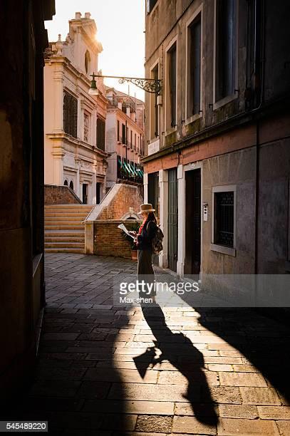 tourist looking at the map in the mazy alley in venice. - véneto fotografías e imágenes de stock