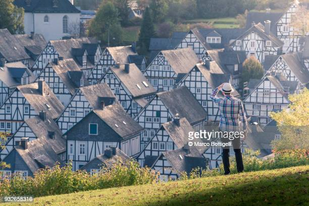 tourist looking at the timber-framed houses of freudenberg, germany. - north rhine westphalia stock pictures, royalty-free photos & images