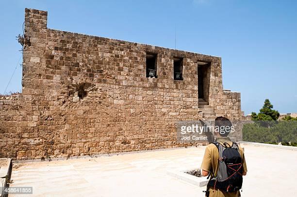 tourist looking at war damage at citadel in tripoli, lebanon - civil war stock pictures, royalty-free photos & images