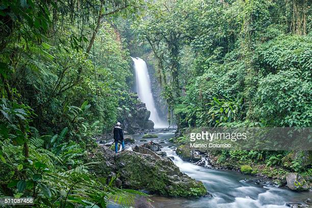 Tourist looking at waterfall in the green rainforest of Costa Rica