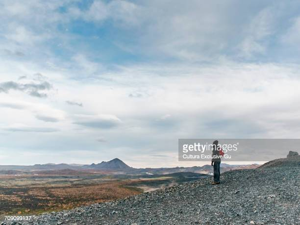 Tourist looking out over sparse landscape, Lake Myvatn, Iceland