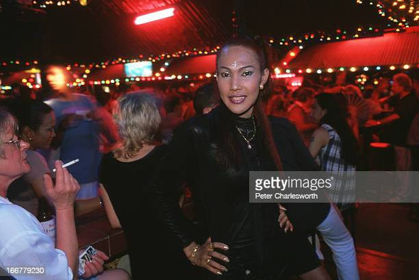 A tourist looks at a posing Katoy or ladyboy transvestite while drinking at one of the hundreds of beer bars in the famous Soi Bangla which is the...