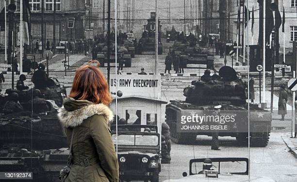 A tourist looks at a poster showing the standoff of Soviet and American tanks at the former Allies' checkpoint at Checkpoint Charlie in Berlin on...
