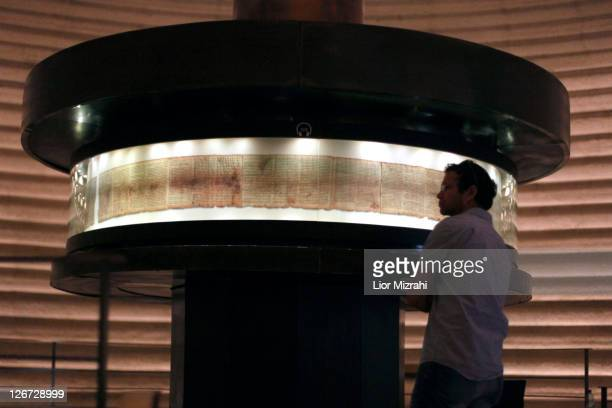 A tourist looks at a replica of the Dead Sea Scrolls on display inside the Shrine of the Book building at the Israel Museum on September 2011 in...