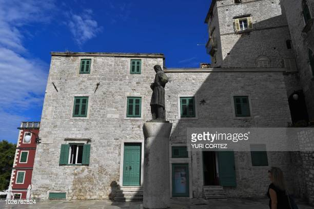 A tourist looks at a statue of Croatian painter Roberto Feruzzi outside the Saint Michael church in the town of Sibenik located in the central area...