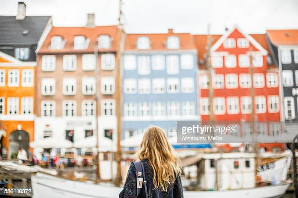 a tourist looks at a view of nyhavn, copenhagen, denmark - copenhague photos et images de collection