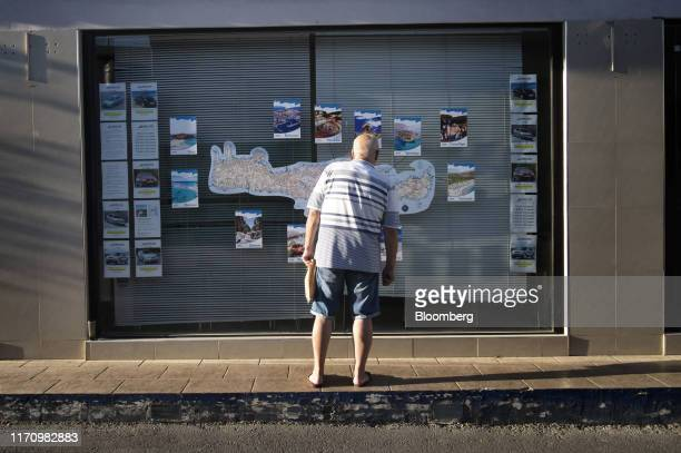 Tourist looks at maps and tourist information displayed on a store window in Hersonissos, on the island of Crete, Greece, on Tuesday, Sept. 24, 2019....