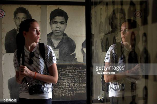 A tourist looks at photos of victims on display at the Toul Sleng Genocide museum July 25 2010 in Phnom Penh province Cambodia The UN backed Khmer...