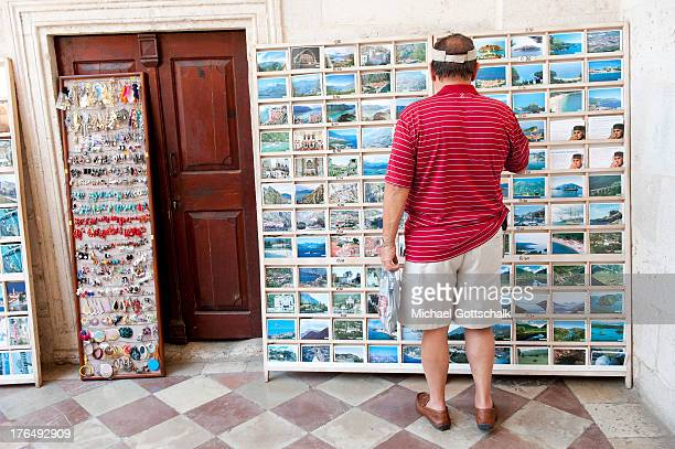A tourist looks at picture postcards displayed in a rack on August 7 2013 in Kotor Montenegro