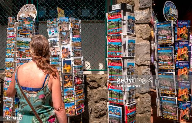 A tourist looks at postcards in the medieval city of Carcassonne on August 9 2019