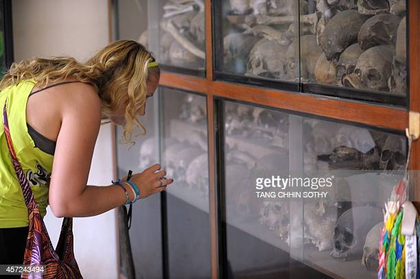 A tourist looks at skulls of the victims of Khmer Rouge displayed for visitors at the Tuol Sleng genocide museum in Phnom Penh on October 15 2014 Two...