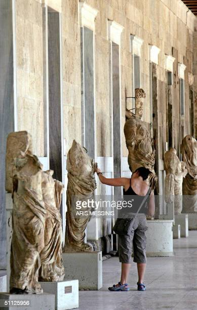 A tourist looks at statues placed inside the ancient Agora's Stoa of Attalos at the foot of Athens' Acropolis hill 29 July 2004 The Stoa is a...