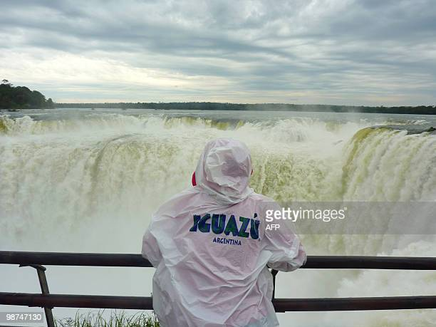 A tourist looks at the Devil's Throat cataract on the Argentinian side of the Iguacu Falls on April 24 2010 The waterfall system consists of 275...