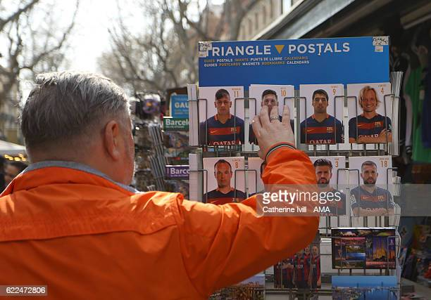 A tourist looks at the postcards of Neymar Lionel Messi Luis Suarez and the FC Barcelona team for sale in a souvenir stall on Las Ramblas on March 15...