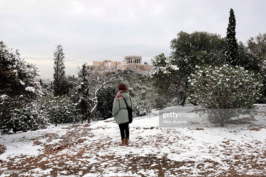 A tourist looks at the Temple of Parthenon which is covered in rare snow on January 10, 2017 in Athens, Greece. Schools in Athens remained closed on Tuesday and the rare snowfall caused traffic disruptions.