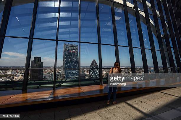 A tourist looks out over The Leadenhall Building also known at the Cheesegrater centre and 30 St Mary Axe also known as The Gherkin right from the...