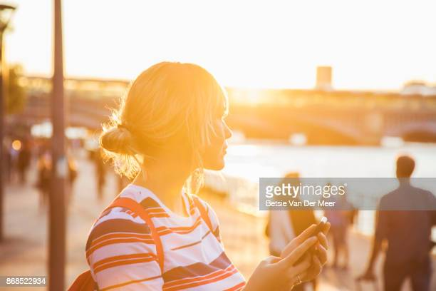 tourist looks out over the urban river skyline,during sunset. - gegenlicht stock-fotos und bilder