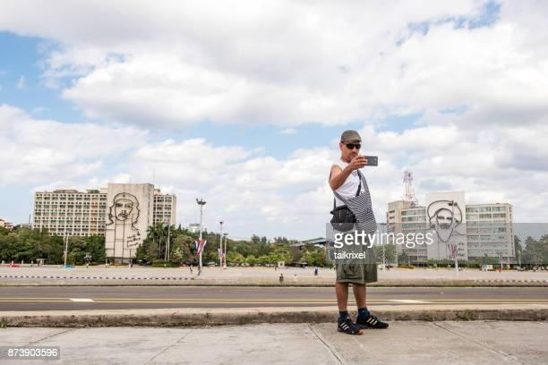 tourist makes selfie at revolution square, havana, cuba - plaza de la revolución havana stock photos and pictures