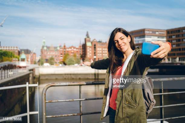 tourist making selfies / vlogging in hafen city - hamburg germany stock pictures, royalty-free photos & images