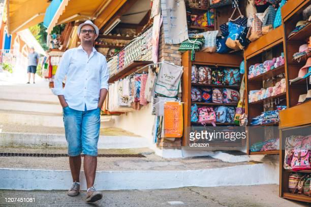 ストリートマーケットでの観光の男 - ギフトショップ ストックフォトと画像