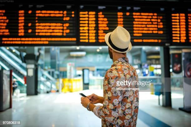 touristischen mann sucht im direktorium zeitplans. - bahnhof fotos stock-fotos und bilder