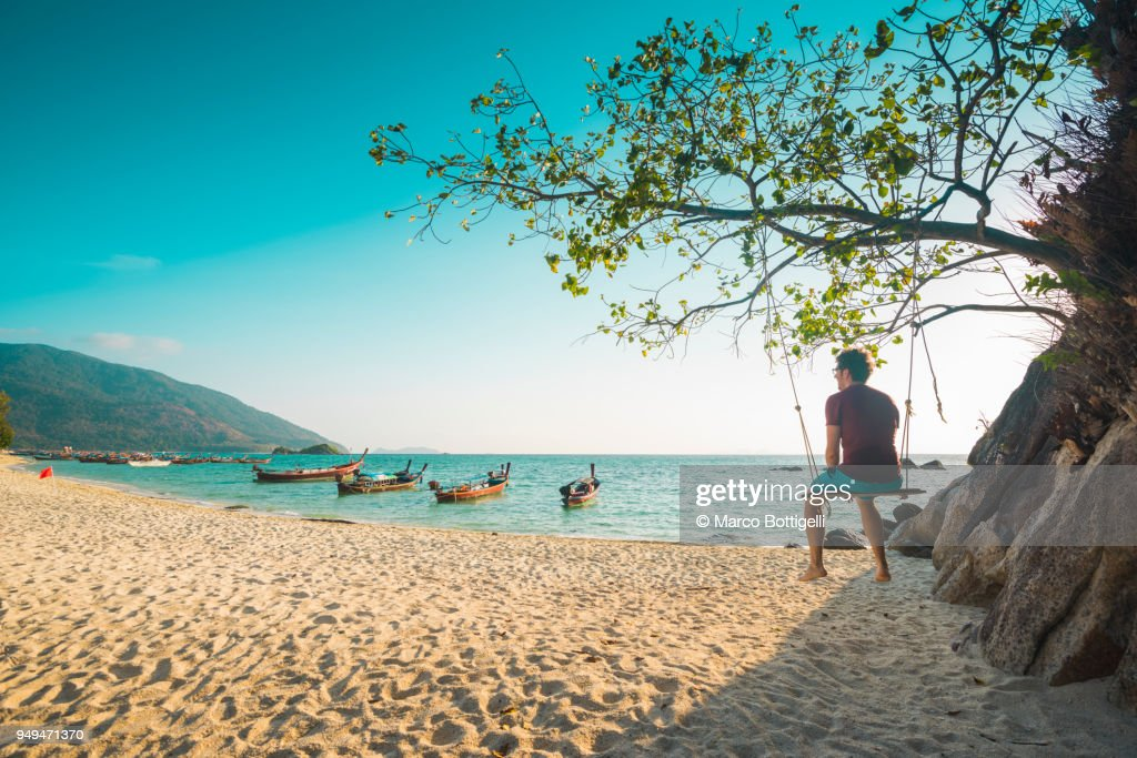 Tourist man sitting on swing at the beach, Thailand : Stock Photo