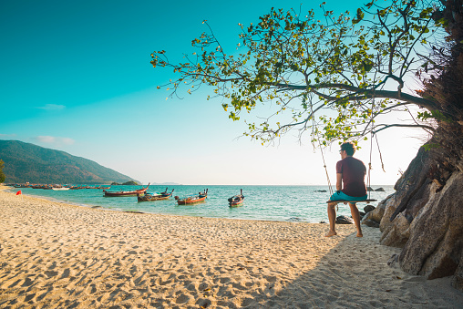 Tourist man sitting on swing at the beach, Thailand - gettyimageskorea