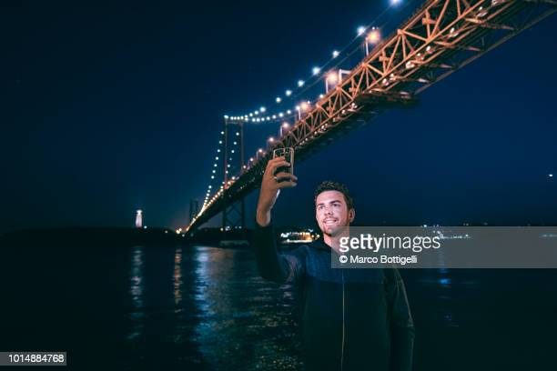Tourist man takes selfie at night at the 25 Abril Bridge, Lisbon, Portugal
