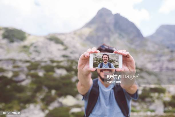 tourist man taking selfie in the mountain - influencer stock pictures, royalty-free photos & images
