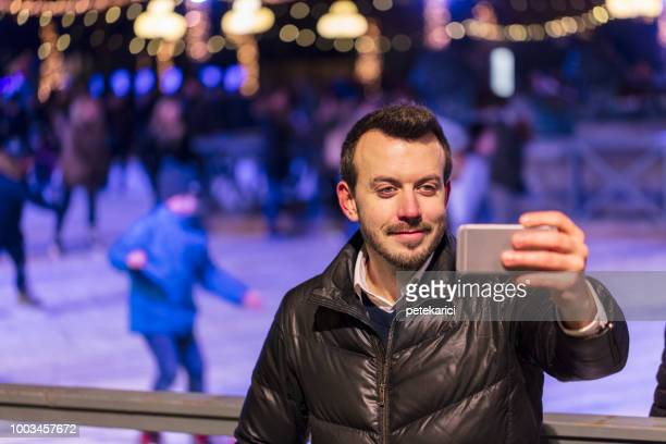 Tourist man taking selfie with ice skaters