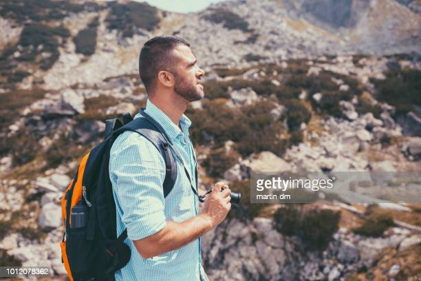 tourist man with camera exploring the mountain - martin dm stock pictures, royalty-free photos & images