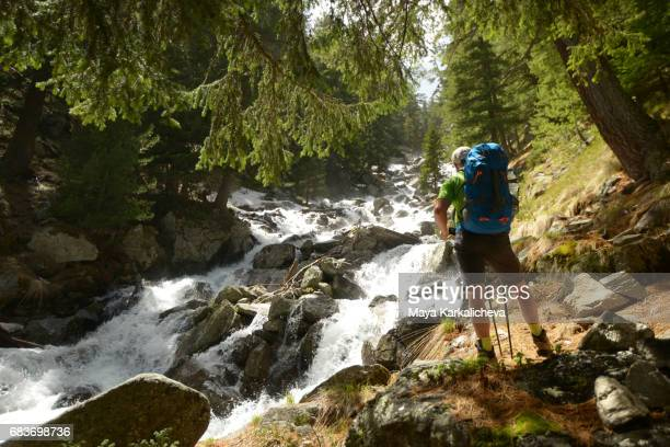 Tourist nearby a strong river in springtime Pirin mountain