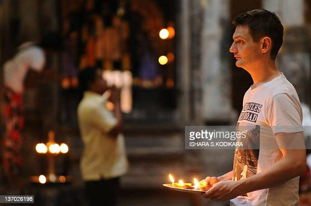 A tourist offers prayers at a Hindu Temple in Colombo on January 15 2012 Hindus in Sri Lanka are celebrating the Thai Pongal festival which is a...