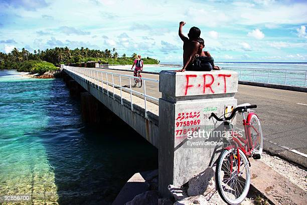 Tourist on a bicycle tour and children playing in a village on September 27 2009 on Fedu Island MaldivesThe maldive islands consist of around 1100...