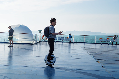 Tourist on a electric monowheel on deck of ferry from Jeju to Mokpo, South Korea - gettyimageskorea