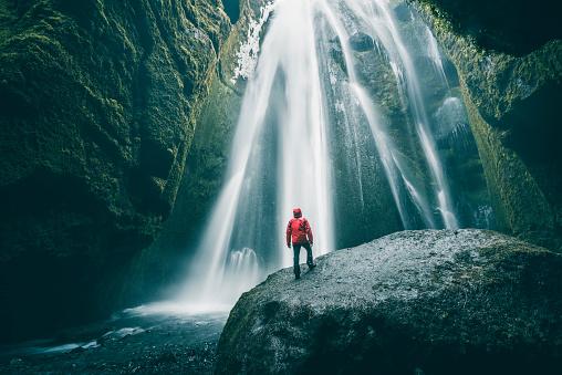Tourist on a rock admiring Gljufrabui waterfall, Iceland - gettyimageskorea