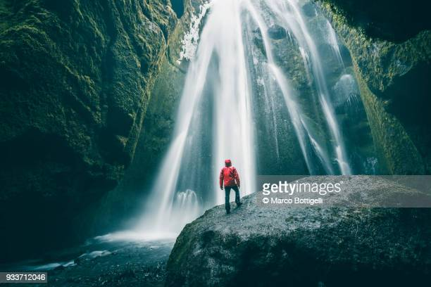 Tourist on a rock admiring Gljufrabui waterfall, Iceland