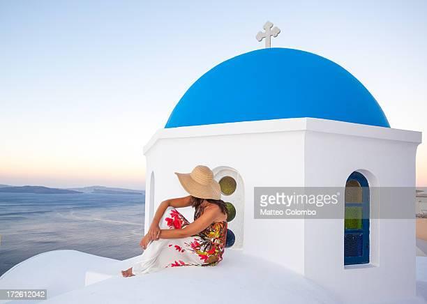 Tourist on blue domed church in Santorini, Greece