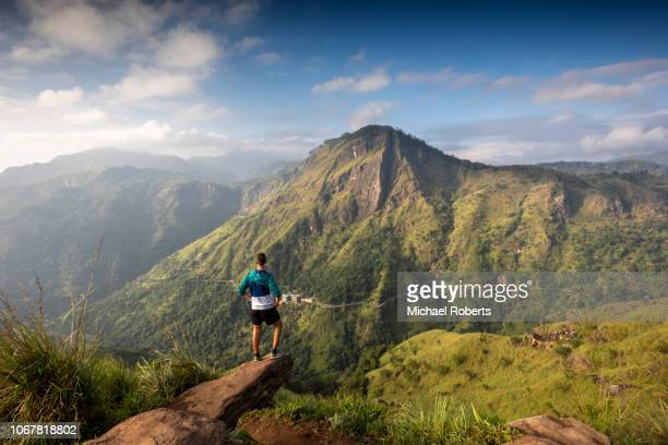 Tourist on Little Adams Peak facing Ella Rock and the Ella Gap in the highlands of Sri Lanka