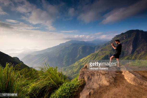 Tourist on Little Adams Peak facing the Ella Gap in the highlands of Sri Lanka