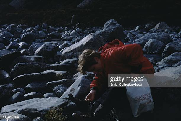 Tourist on rocks with Qantas Airlines bag New Zealand 1961